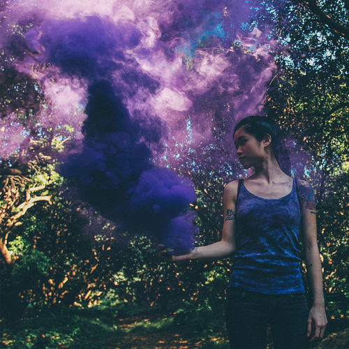 Young Woman With Purple Smoke Bomb In Forest