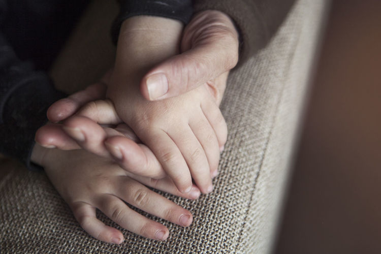 Grandfather And Grandson Holding Hands Close-up