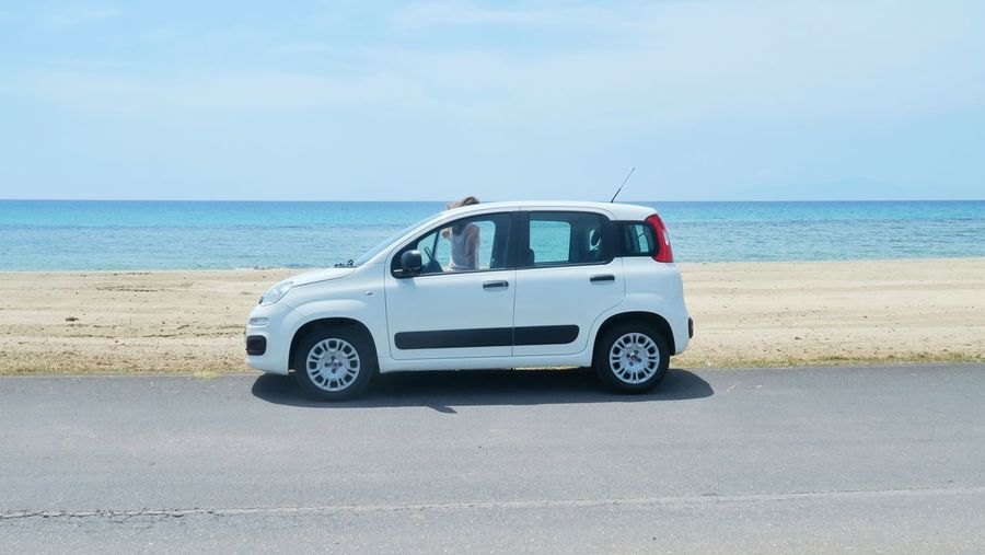 Small white car in front of an empty beach in Nea plagia, greece White Car Traveling Empty Greece Nea Plagia Vacations Holiday Summer Hot Weather Sunny Water Clear Sky Sea Beach Sand Dune Desert Sand Coastline