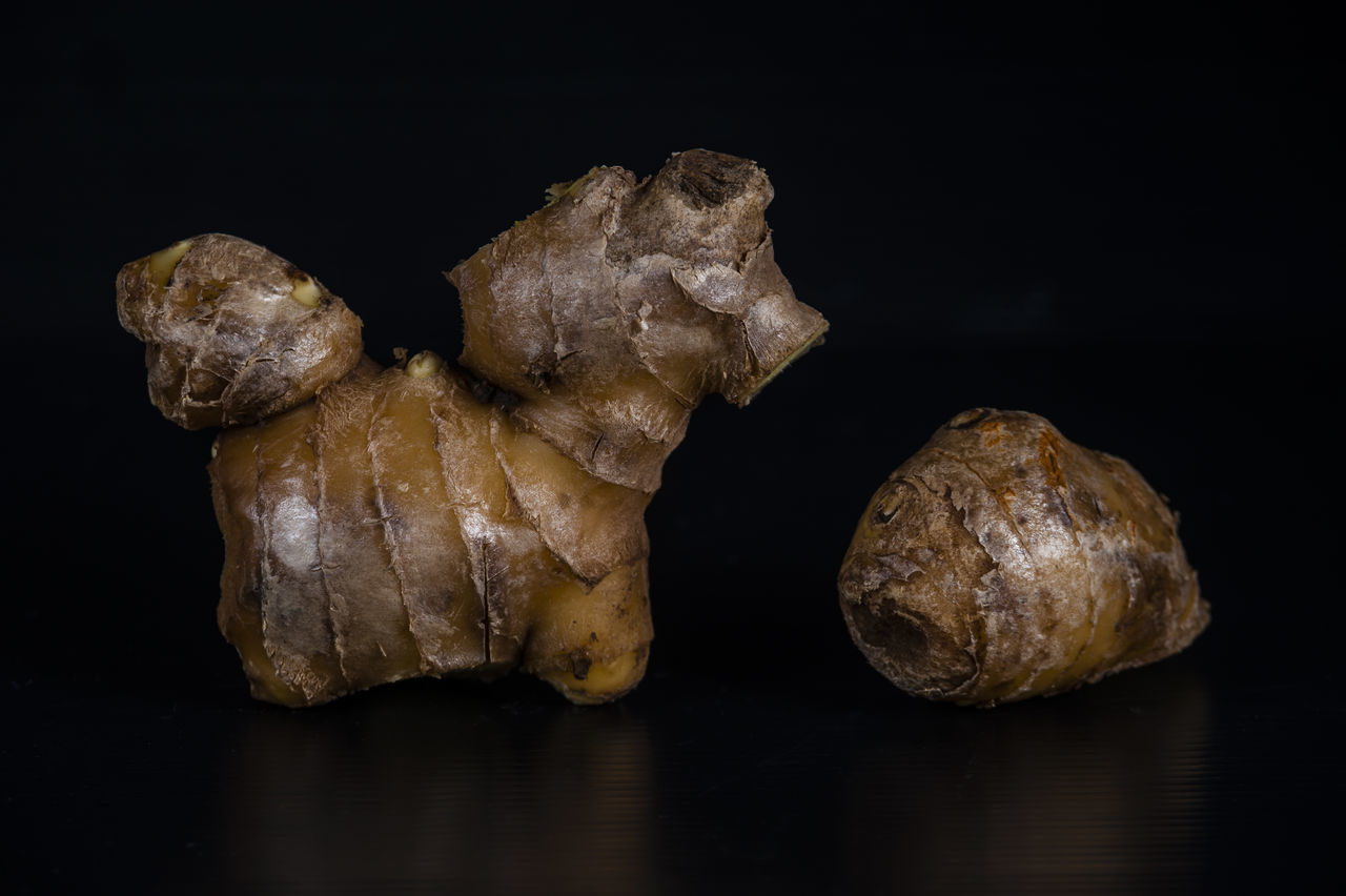 Close-Up Of Ginger On Table Against Black Background