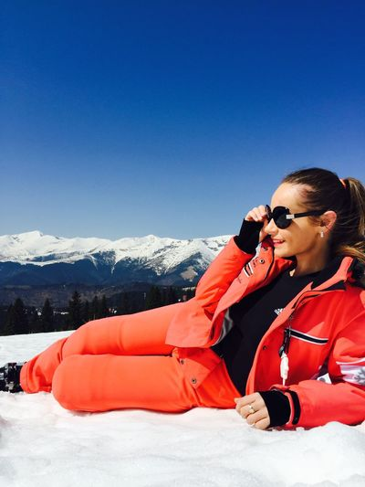 Young Woman Lying On Snowcapped Mountain Against Clear Sky
