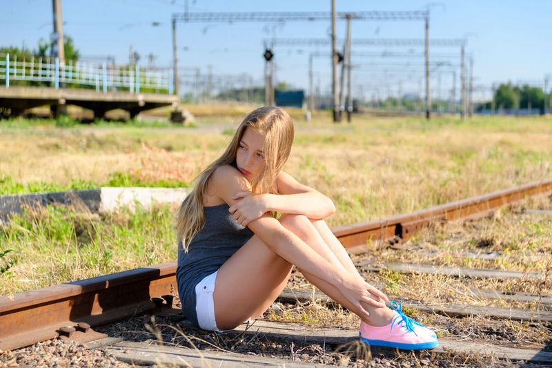 Lonely and sad teenager girl sitting on rusty rail track in the countryside. Adolescence problems Blonde Caucasian Concrete Day Female Girl Horizontal Nature Outdoors Pensive Person Problem Railroad Railway Rusty Sad Shorts Sit Summer Teen Teeneger Youth