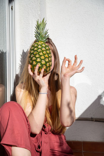 Young cheerful sensual woman in casual summer dress holding tropical pineapple with closed eyes and showing ok gesture Woman Pineapple Ok Gesture Happy Smiling Recommend Approve Balcony Terrace Summer Young Female Joy Cheerful Beautiful Attractive Pretty Charming Sensual_woman Cool Casual Dress Food Fruit Tropical Exotic Healthy Ripe Tasty Sweet Juicy Fresh Organic Natural Vitamins Leaning Sitting Holding Vertical Copy Space