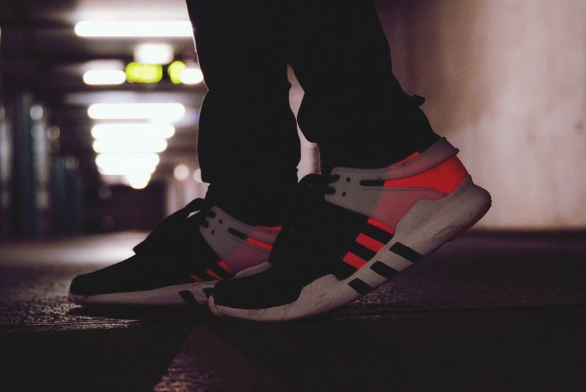Low Section Human Leg Indoors  Close-up People Adult Adidas Eqt Urban Parking Lot Parking Garage Illuminated Multi Colored Focus On Foreground