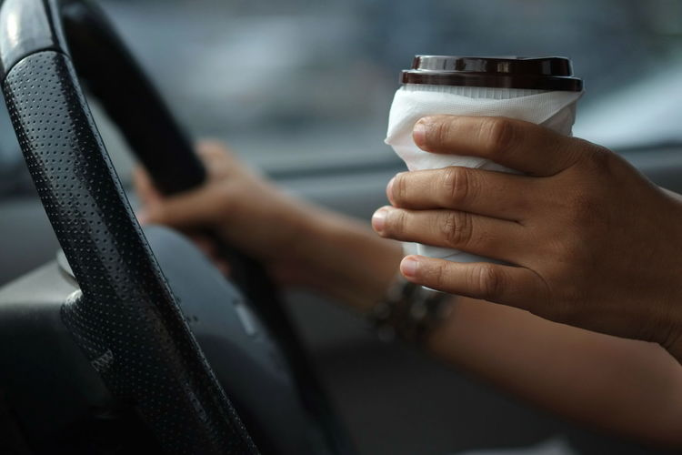 A woman holding a coffee mug with the other hand holding a steering wheel while driving in a hurry. Busy Caffeine Hot Lifestyle Morning People Watching Rush Traffic Aroma Brverage Car Careless Close-up Concept Day Distracted Drink Finger Hand Holding Lifestyles Motor Vehicle People Transportation Women