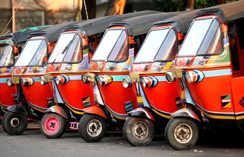 Rickshaws parked in row on street at city