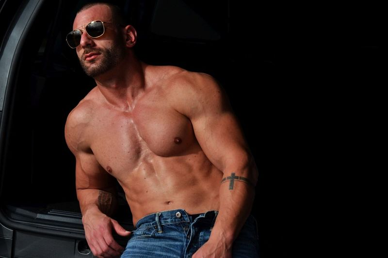 Shirtless muscular man leaning on car trunk