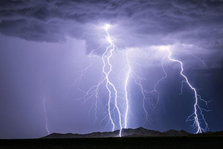 Lightning bolts strike a mountain as a thunderstorm drifts through the desert near phoenix, arizona.
