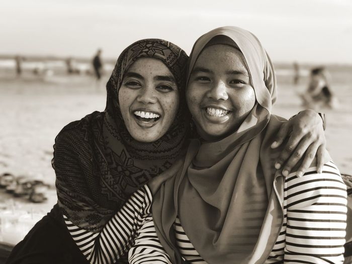 Close-up portrait of smiling friends wearing hijab at beach