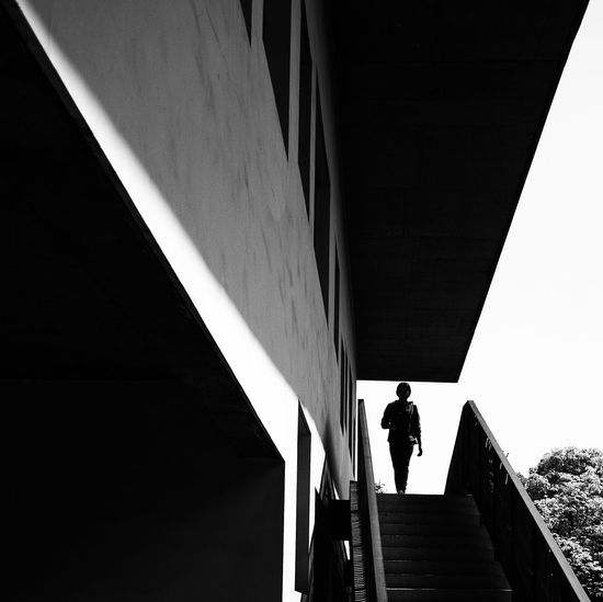Low angle view of silhouette man standing on staircase against building