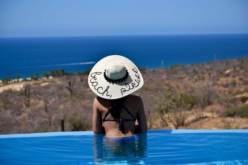 Rear view of woman relaxing in infinity pool against clear sky during sunny day