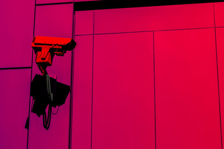 Low Angle View Of Security Camera Against Pink Wall