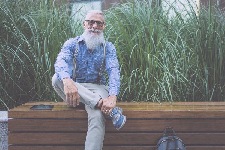 Senior hipster sitting against plants