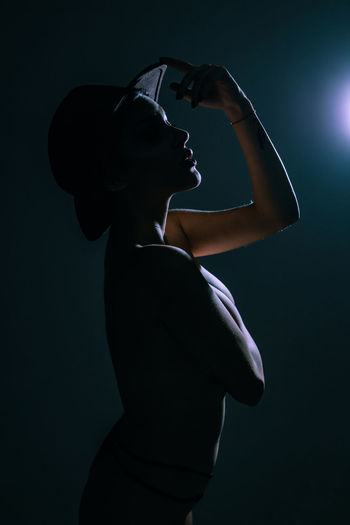 Side view portrait of young woman standing against black background