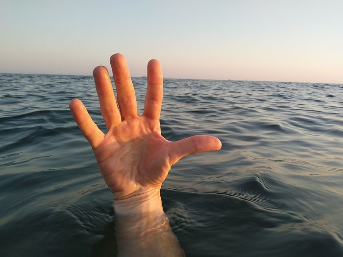 Cropped hand of man in sea against sky