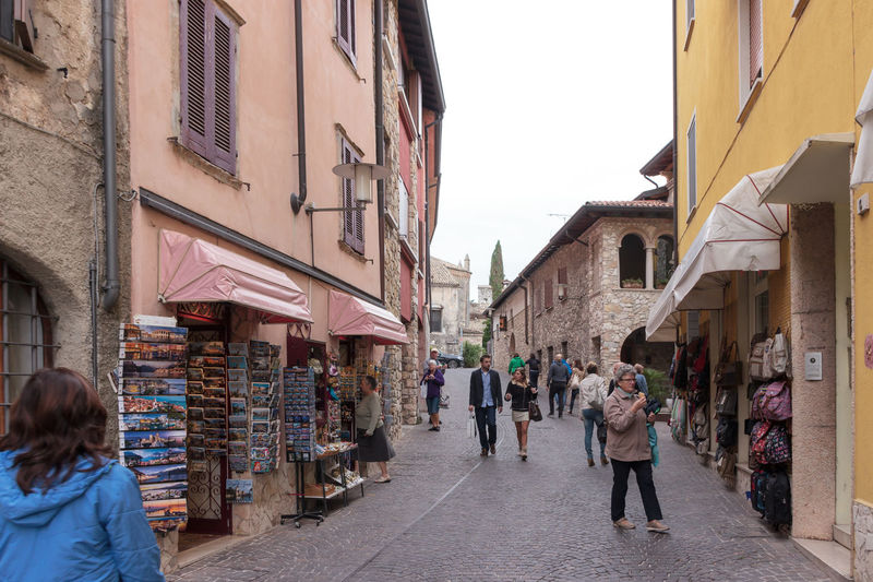 Sirmione, Italy - October 01, 2015 : Tourists walk the streets of the city and inspect local attractions in Sirmione, Italy Architecture Building Castello Castle Day Destination Europe Famous Fortification Fortress Garda Italy Lago Lake Lombardy Medieval Old Outdoors Scaliger Sirmione Tourism Tower Travel Wall Water