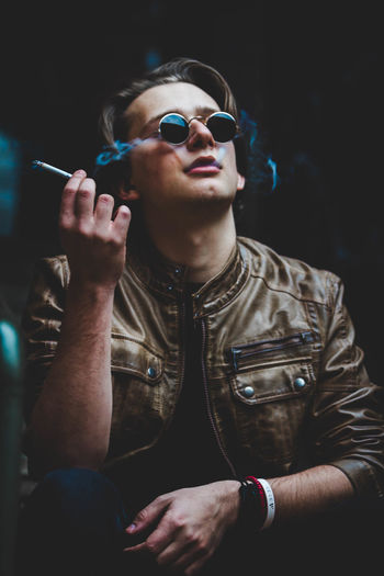 Close-up of man wearing sunglasses smoking cigar
