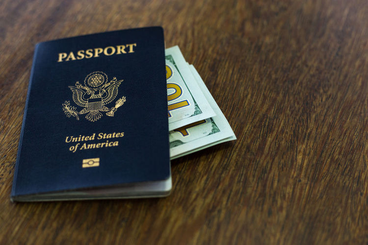 Blue American passport with US dollars American Cochabamba Currency Desk North America Passport Travel Traveling US Passport USA USD United States America Close-up Communication Day Document Dollar Indoors  Money No People Passport Table Text Wooden
