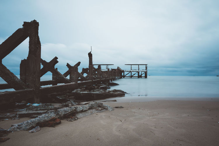 Abandoned wooden structure on beach against sky