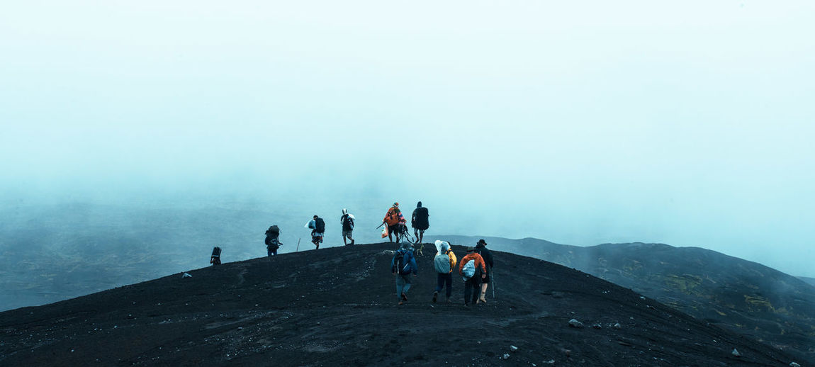 People Hiking On Mountain During Foggy Weather