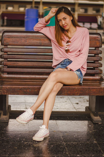 Portrait of smiling mid adult woman sitting on bench