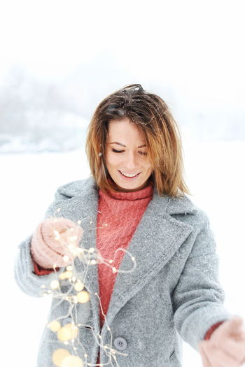 Young Woman Holding Illuminated String Lights While Standing On Snow Covered Field