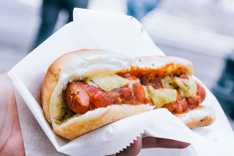 Cropped Image Of Hand Holding Hot Dog