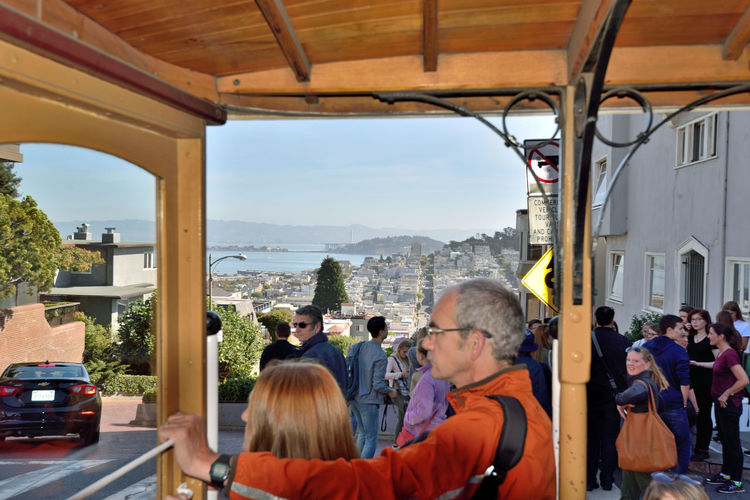 Riding The Hyde Street Cable Car 2 San Francisco CA🇺🇸 Hyde/Powell Cable Car Streets Of San Francisco Cable Car Viewpoint Grip Car Manually Operated Down Hill Car Scenic View People Watching People On Board Background Yerba Buena Island Bay Bridge San Francisco Bay Eastbay Hills City Housing San Francisco Municipal Railway MUNI Architect : Andrew Smith Hallidie 1873 Intermodal Urban Transport Network Powell-Hyde St Line Est 1957 Fisherman's Wharf National Register Of Historic Places 66000233