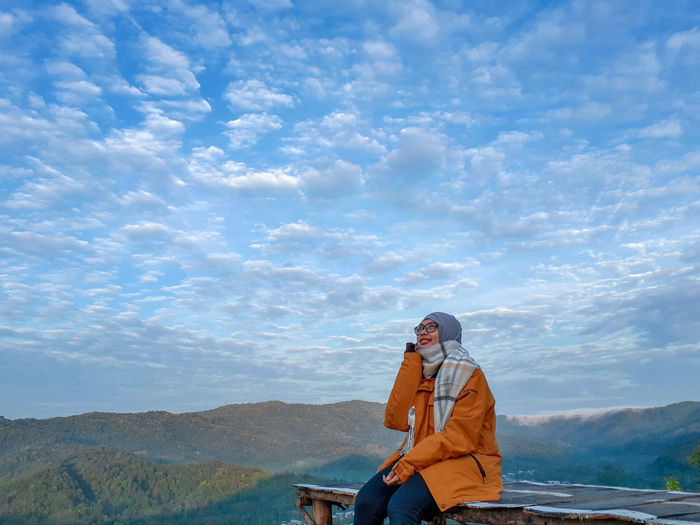 Young woman in warm clothing sitting on observation point against cloudy sky