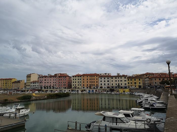 High angle view of buildings by river against cloudy sky