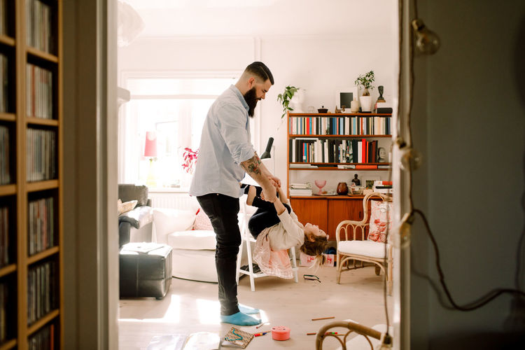 Side view of man standing at home