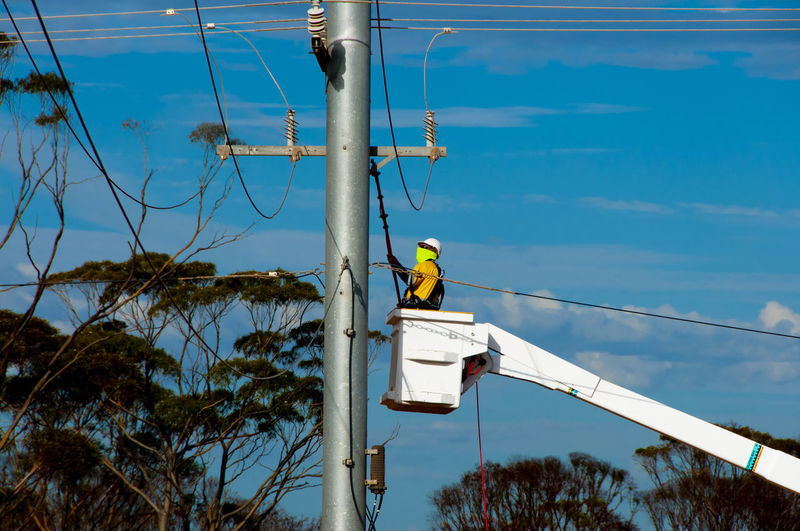 Man working on electrical pole against sky