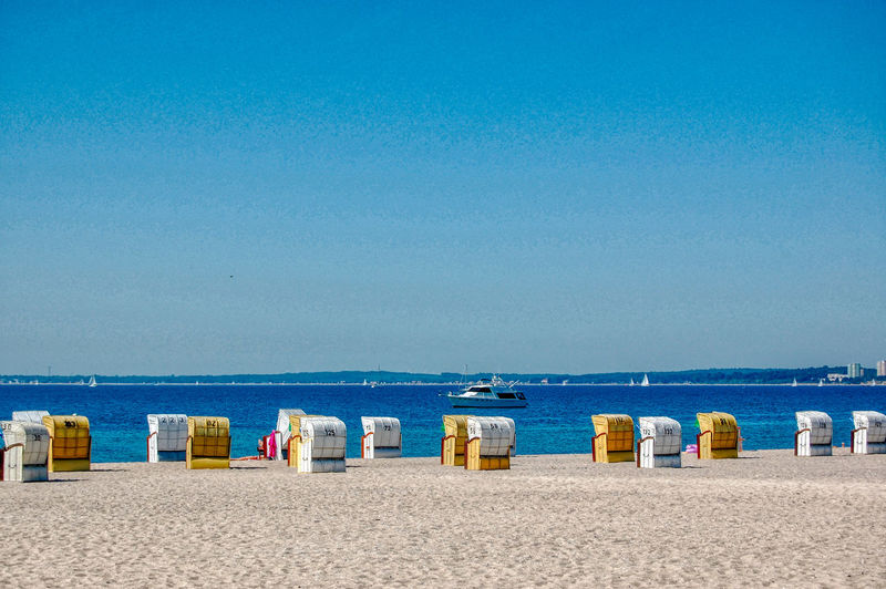 Hooded chairs on beach against clear blue sky