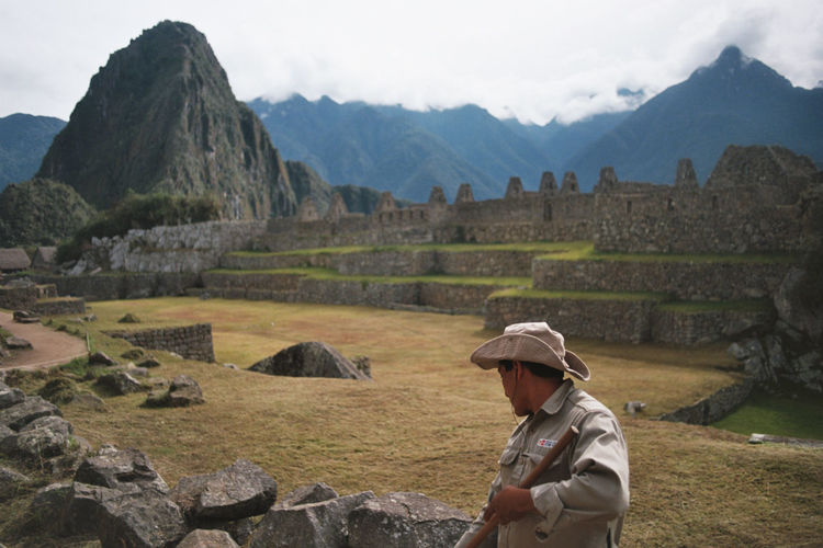 Sanitation worker cleaning field at machu picchu