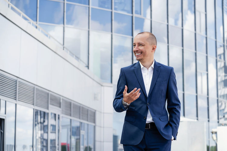 Smiling mid adult man standing in front of office building