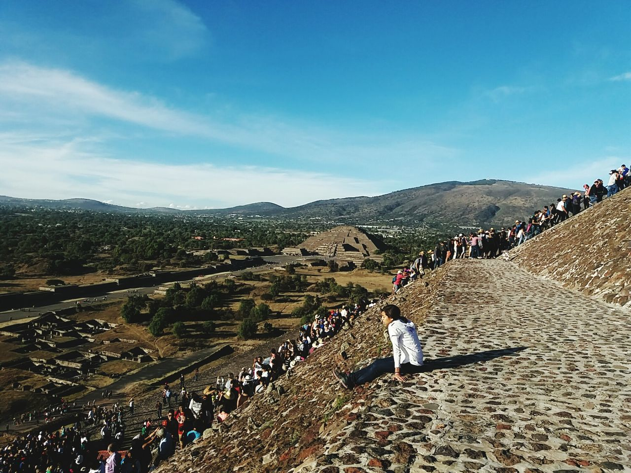 large group of people, real people, women, leisure activity, lifestyles, men, mountain, mixed age range, high angle view, day, crowd, outdoors, travel destinations, history, nature, ancient civilization, ancient, sky, built structure, vacations, pyramid, architecture, beauty in nature, adult, people, adults only