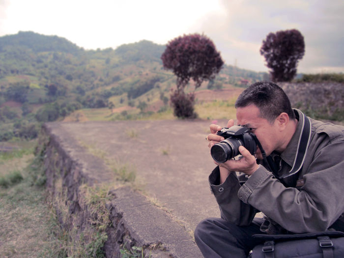 Close-up of man photographing on road using camera