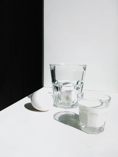 Close-up of empty glass on table against white background