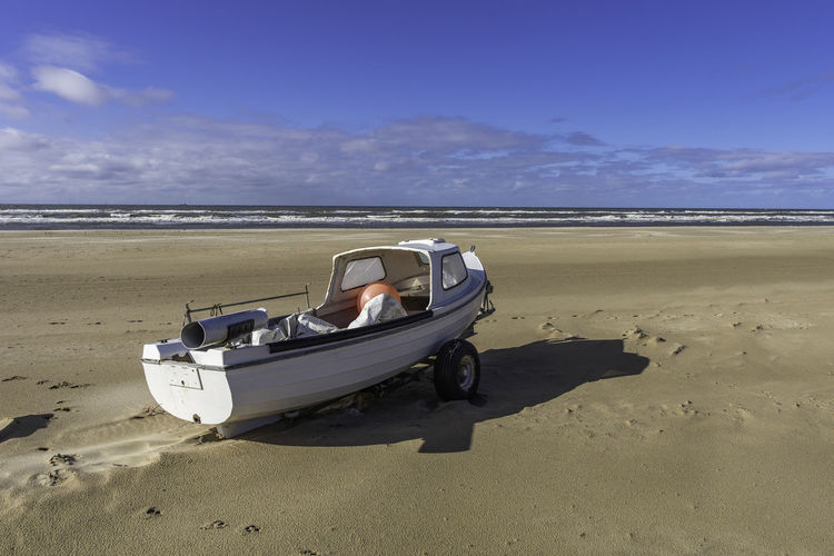 Nautical vessel on beach against sky