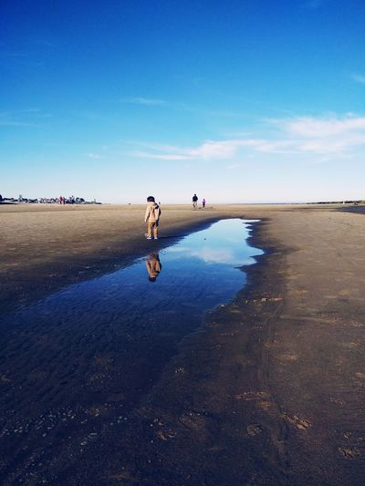 Boy reflecting in water at beach