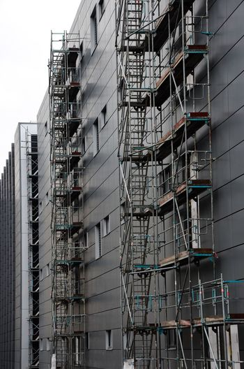 Low angle view of buildings in city with scaffolding