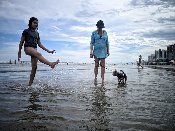 Yorkshire Yorkshire Terrier Beach International Women's Day 2019 Water Pets Full Length Togetherness Friendship Young Women Sea Beach Bonding Ankle Deep In Water Swimming Trunks Splashing Wave Retriever