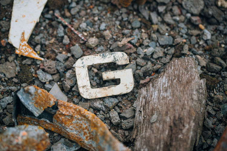 Close-up Metal Deterioration Directly Above Rock Rock - Object Rough Stone - Object Textured  Wood - Material Selective Focus Letter Growth Letter G On The Ground