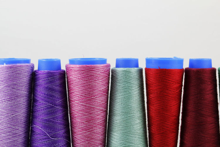 Colorful sewing coils isolated on white background Sewing Embroidery Bobbin Background DIY Craft Isolated White Textile Thread Machine Sew Coil Colorful Fashion Material Fiber Spool Color Cotton Product Clothing Hobby Reel Vintage Factory Industry Designer  String Manufacturing Manufacture