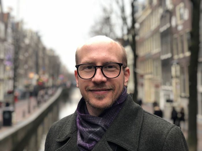 Portrait Of Smiling Bald Man Standing In City
