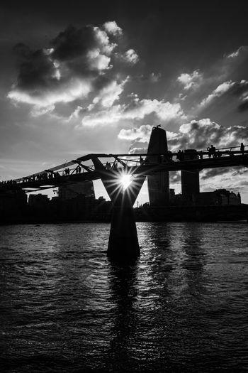 Silhouette bridge over river against sky in city