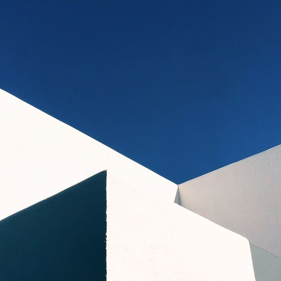 High Section Of White Wall Against Clear Blue Sky