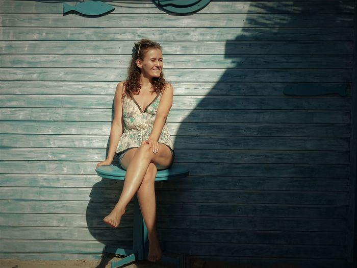 Young woman wearing sunglasses sitting on table against blue wooden wall