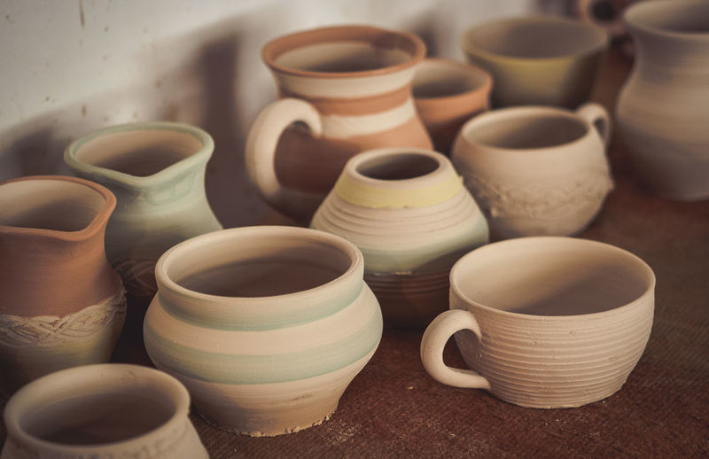 Many clay pot is on the table in pottery. bright pottery. many white, not painted clay pottery ste.
