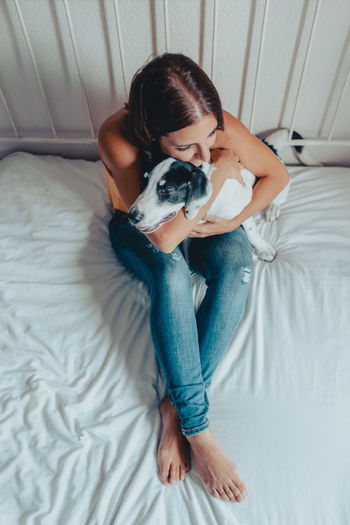 High angle view of woman with dog on bed at home